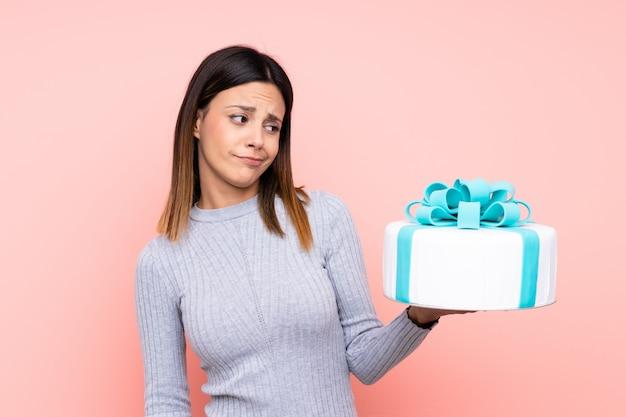 Kobieta trzyma duży tort nad menchii ścianą z smutnym wyrażeniem