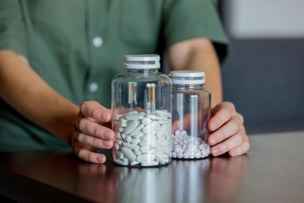 Kobieta trzyma dwa słoiki białych tabletek na stole w domu