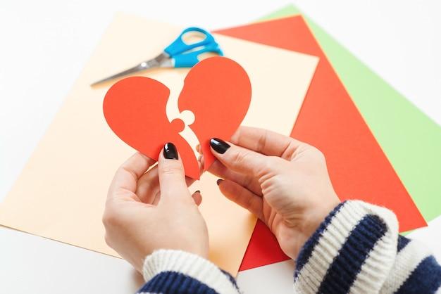 Kobieta trzyma dwie części papierowego serca. szczęśliwych walentynek.