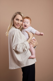 Kobieta trzyma dziecko w ramionach. portret młodej matki po urodzeniu dziecka. młoda rodzina