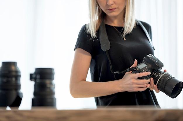 Kobieta trzyma fachową kamerę i obiektyw