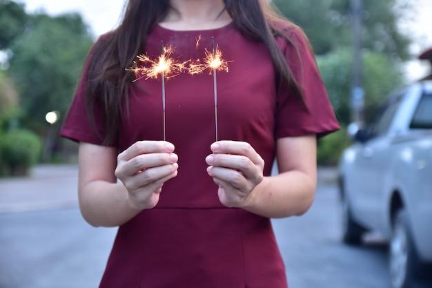 Kobieta trzyma fajerwerk blask na wieczór