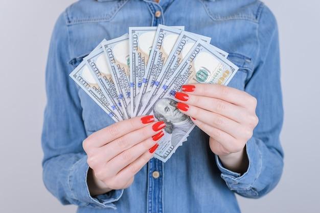 Kobieta trzyma fanem pieniędzy na białym tle szarym tle