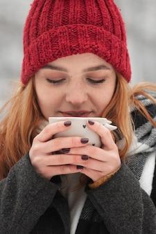 Kobieta trzyma filiżankę herbaty i bierze łyka