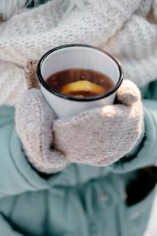Kobieta trzyma filiżankę herbaty na zewnątrz w zimie