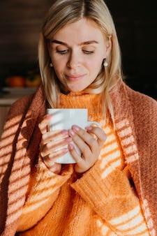 Kobieta trzyma filiżankę herbaty