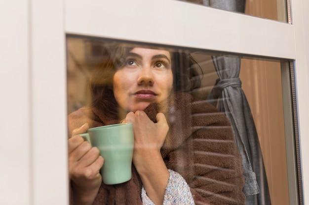 Kobieta trzyma filiżankę kawy, będąc przykryta kocem