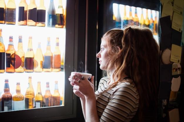 Kobieta trzyma filiżankę kawy i patrząc na wyświetlacz wina
