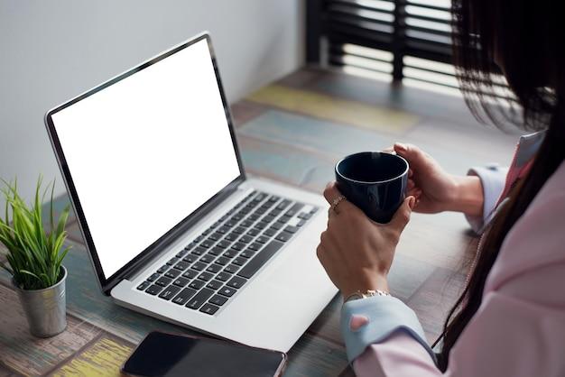 Kobieta trzyma filiżankę kawy i pracuje z laptopem w biurze. makieta