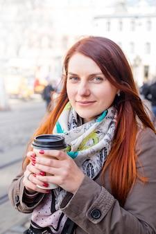 Kobieta trzyma filiżankę kawy i uśmiech na niewyraźnej ulicy. słoneczne wiosenne popołudnie.