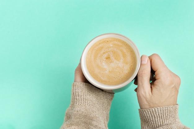 Kobieta trzyma filiżankę kawy na modnym kolorze niebieskim tle.