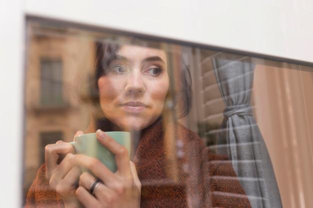 Kobieta trzyma filiżankę kawy, patrząc na zewnątrz