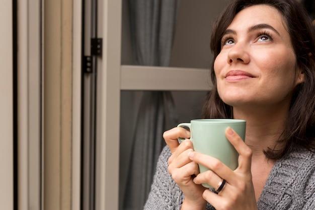 Kobieta trzyma filiżankę kawy, patrząc w górę