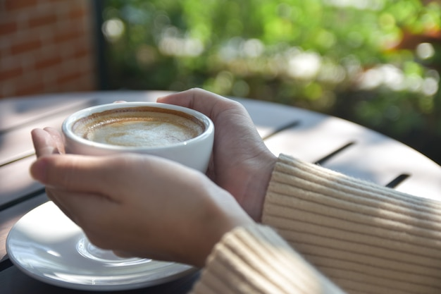 Kobieta trzyma filiżankę kawy przy kawiarnią