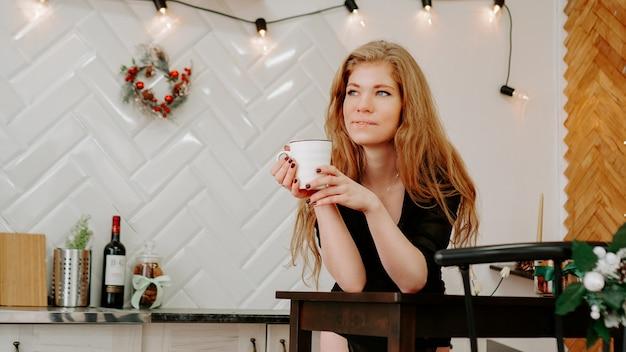 Kobieta trzyma filiżankę kawy rano w boże narodzenie kuchni. szczęśliwa młoda kobieta bawi się i uśmiecha