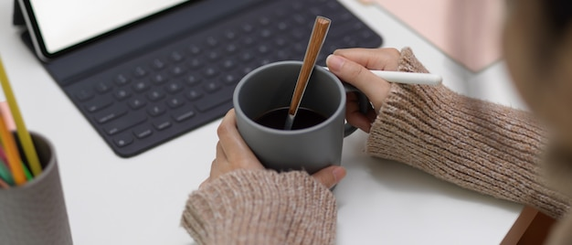Kobieta trzyma filiżankę kawy w biurze