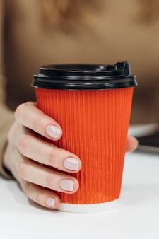 Kobieta trzyma filiżankę kawy w pracy z bliska