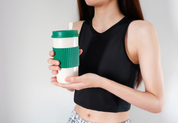 Kobieta trzyma filiżankę kawy w ręce z ćwiczeń dziewczyny tło.