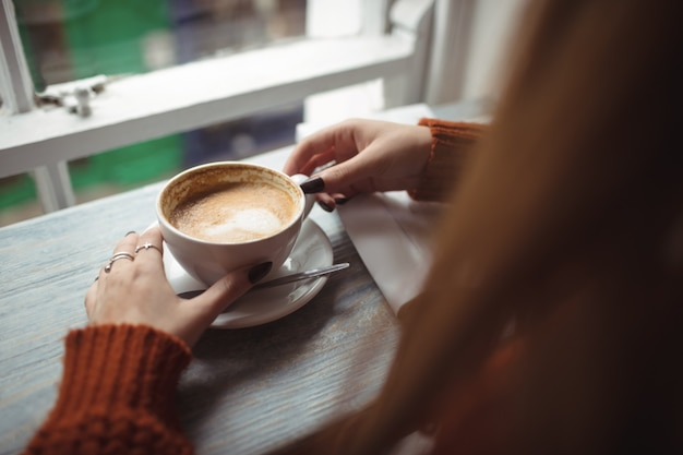 Kobieta trzyma filiżankę kawy