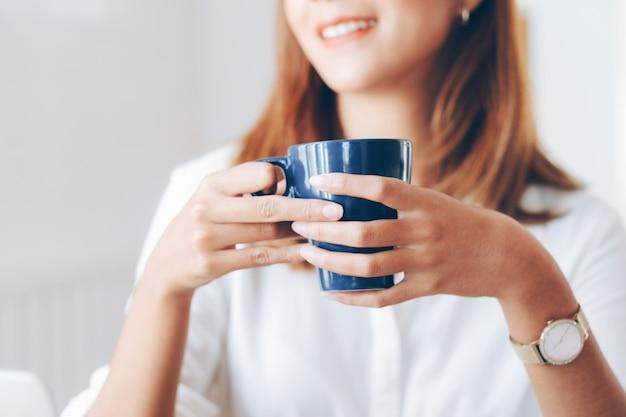 Kobieta trzyma filiżankę kawy.