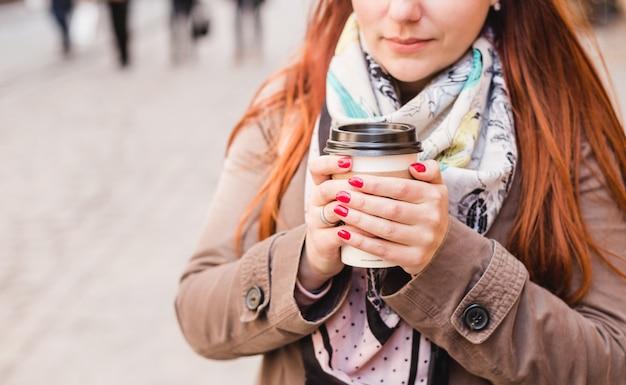 Kobieta trzyma filiżankę na zamazanej ulicie. słoneczne wiosenne popołudnie. czerwony manicure. żeńska ręka z papierową filiżanką kawy zabiera.