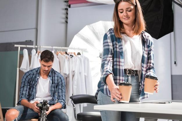 Kobieta trzyma filiżanki kawy obok fotografa