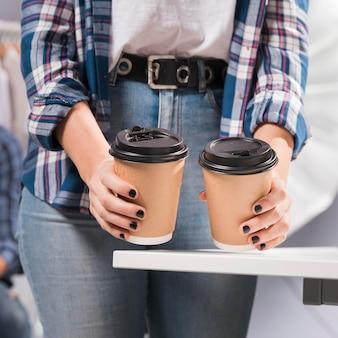 Kobieta trzyma filiżanki kawy w studiu