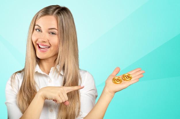 Kobieta trzyma fizyczną kryptowalutę bitcoin