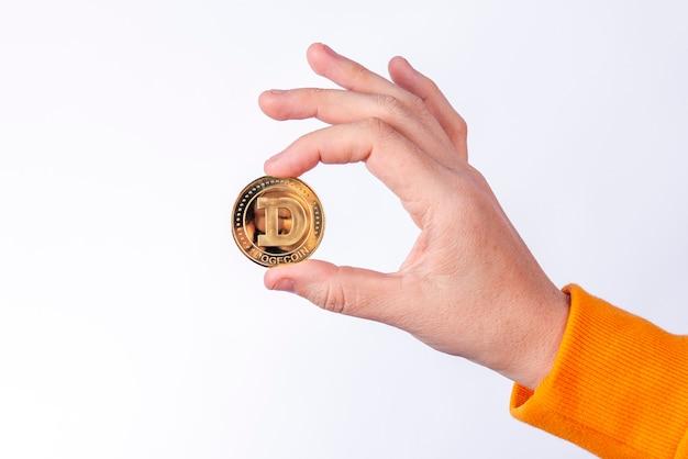 Kobieta trzyma fizyczną monetę 1 dogecoin (doge). koncepcje kryptowalut na białym tle.