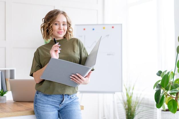 Kobieta trzyma folder na papier pisać znacznik myślenia marzy, stojąc w pobliżu biurowego stołu. biznesmen femal ypoung dorosły kaukaski na nowoczesnym białym wnętrzu