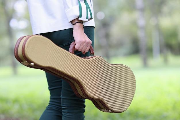 Kobieta trzyma futerał na skrzypce i gitarę i spaceruje przez ulicznych muzyków parkowych i samotność