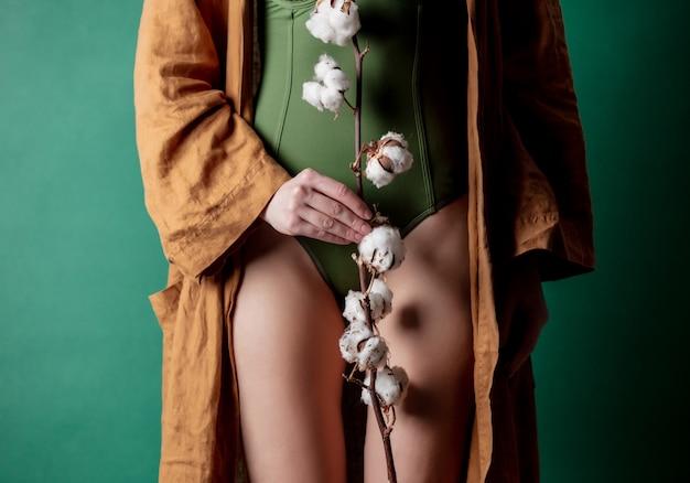Kobieta trzyma gałęzi bawełny w jej ręce na poziomie stóp