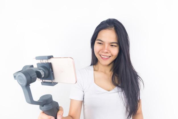 Kobieta trzyma gimbal lub stabilizator z telefonem komórkowym