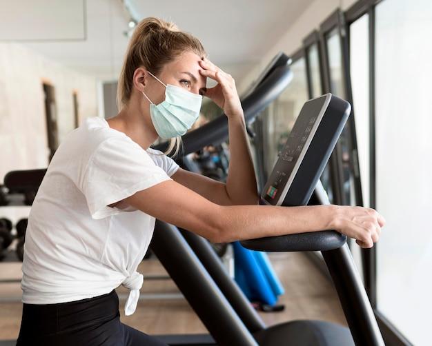 Kobieta trzyma głowę ręką na siłowni