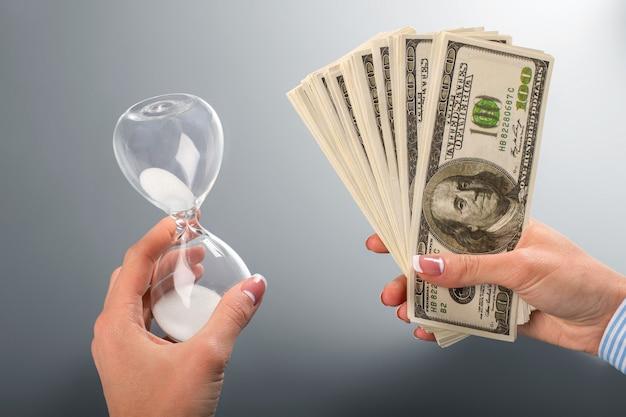Kobieta trzyma gotówkę i klepsydrę. wachlarz lady's klepsydra i dolar. musi wziąć je obie. zawsze wybieraj mądrze.