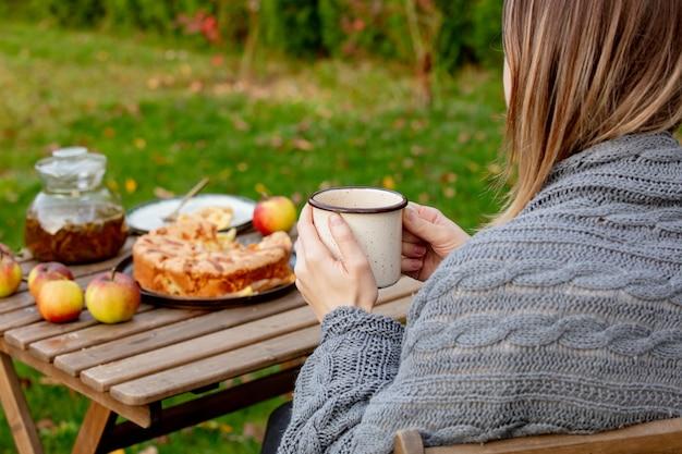 Kobieta trzyma herbacianą filiżankę i siedzi blisko stołu z jabłczanym kulebiakiem w ogródzie