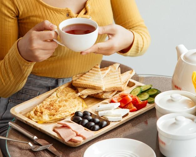 Kobieta trzyma herbacianą filiżankę przy śniadaniowym stołem