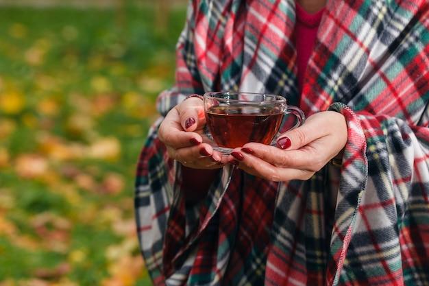 Kobieta trzyma herbatę w parku jesień