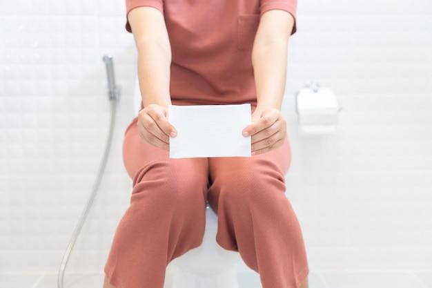 Kobieta trzyma higieniczne pieluchy i obsiadanie na toalecie - kobieta na jej okresie