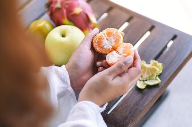 Kobieta trzyma i obiera pomarańczę do jedzenia z gruszką i owocem smoka na małym drewnianym stole
