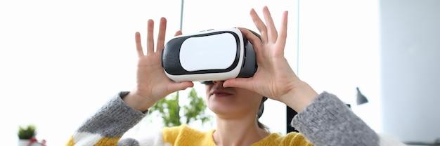 Kobieta trzyma i ogląda wideo w okularach wirtualnej rzeczywistości