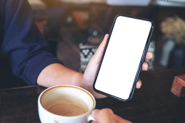 Kobieta trzyma i pokazuje czarny telefon komórkowy z pustym ekranem komuś na stole w kawiarni