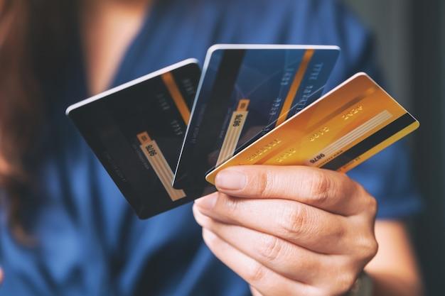 Kobieta trzyma i pokazuje karty kredytowe
