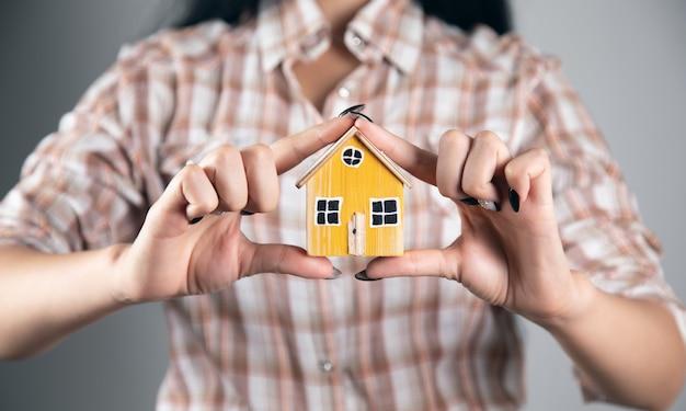 Kobieta trzyma i pokazuje model drewnianego domu
