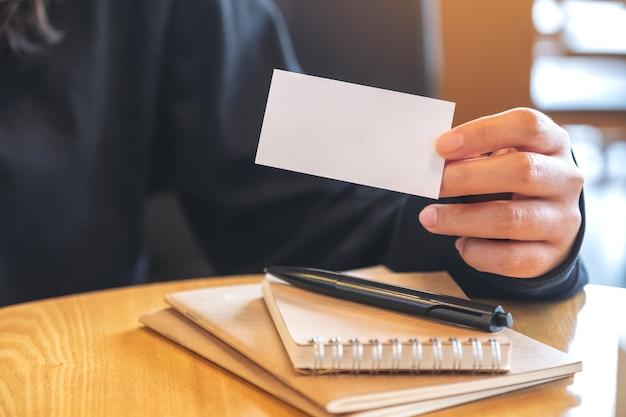 Kobieta trzyma i pokazuje pustą wizytówkę z notatnikami na stole