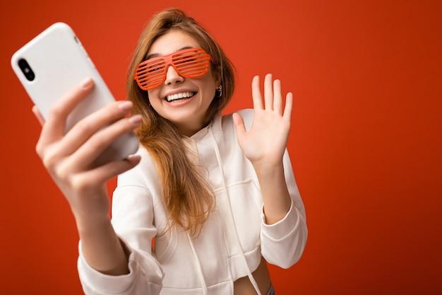 Kobieta trzyma i przy użyciu telefonu komórkowego przy selfie na sobie stylowe ubrania na białym tle na tle ściany.