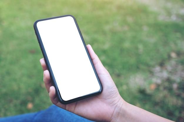 Kobieta trzyma i używa czarnego smartfona z pustym białym ekranem na zewnątrz