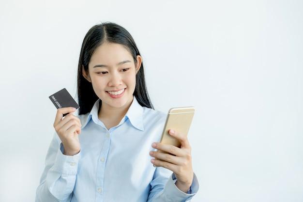 Kobieta trzyma i używa karty kredytowej do zakupów online z domu za pomocą smartfona, płatności e-commerce, bankowości internetowej, wydawania pieniędzy na następne wakacje.