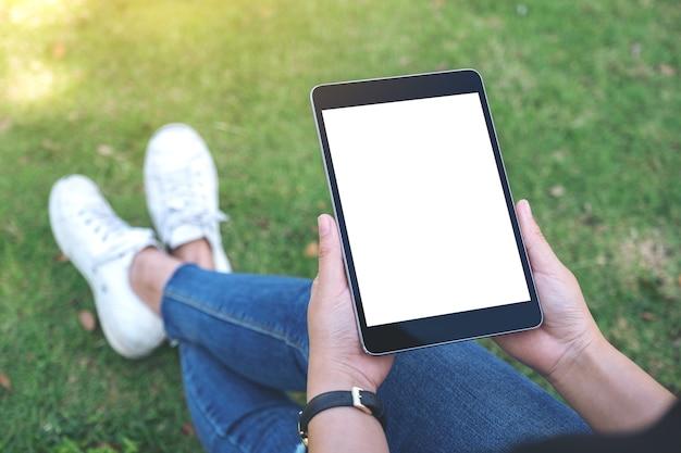 Kobieta trzyma i za pomocą czarnego komputera typu tablet z pustym białym ekranem poziomo, siedząc w parku