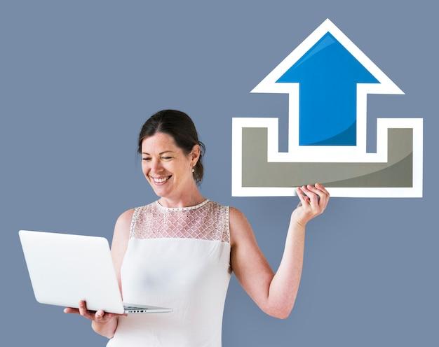 Kobieta trzyma ikonę przesyłania i laptopa
